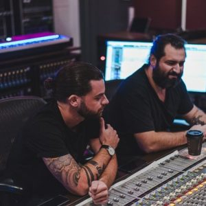 Matt Salazar And Lucas Flood Sitting In Front Of An SSL 8000G+ Console At IFMG Studios